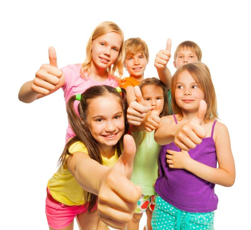 Porträt von sechs Kindern, die sich Daumen zeigen stockbild