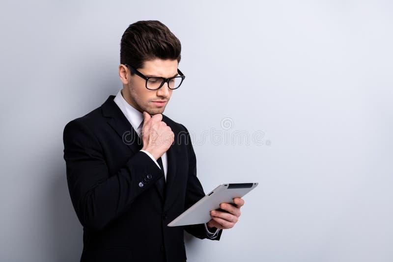Porträt von seinem er nettes imponierendes elegantes nobles attraktives nachdenkliches Kerl neues digitales ebook surfendes Websi stockfotografie