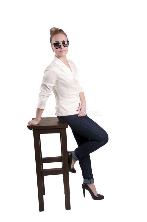 Porträt von tragenden Gläsern einer schönen Geschäftsfrau auf einem Stuhl lokalisiert stockfotografie