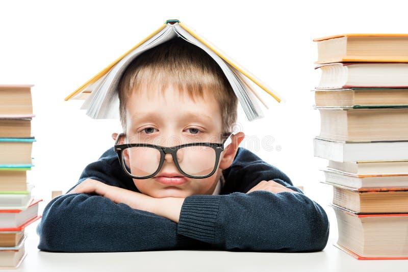 Porträt von tragenden Gläsern eines müden Schülers mit einem Buch auf seinem lizenzfreie stockbilder