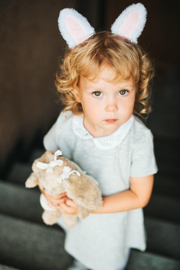 Porträt von tragenden Häschenohren des entzückenden Kleinkindmädchens stockfoto