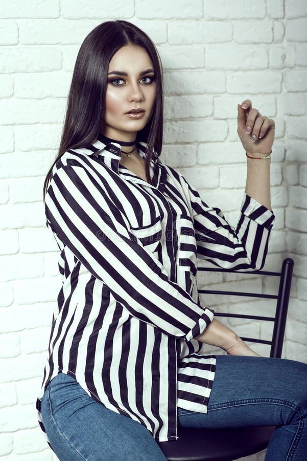 Porträt von tragenden Jeans des jungen herrlichen dunkelhaarigen Modells, von gestreiftem Hemd mit Taschen und von schwarzem Hals stockbilder