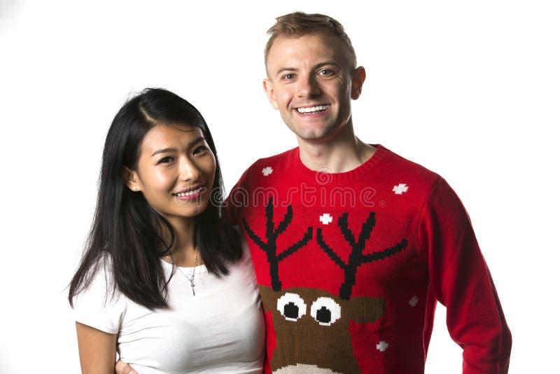Porträt von tragenden Pullovern der glücklichen multiethnischen Paare Weihnachtsim Studio stockfotografie