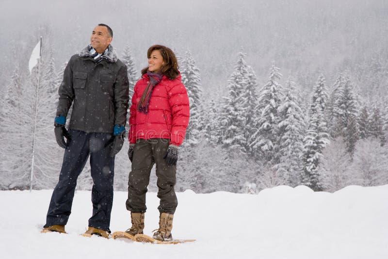 Porträt von tragenden Schneeschuhen eines reifen Paares lizenzfreie stockfotografie