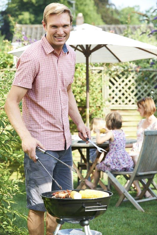 Porträt von Vater-Cooking Barbeque For-Familie im Garten zu Hause lizenzfreie stockfotografie