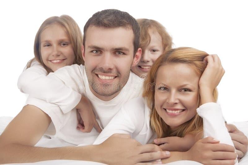 Porträt von vier kaukasischen Familienmitgliedern, die sich im weißen Cl hinlegen lizenzfreie stockfotografie