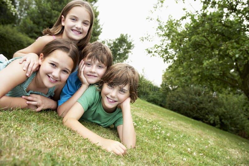 Porträt von vier Kindern, die im Park liegen stockbilder