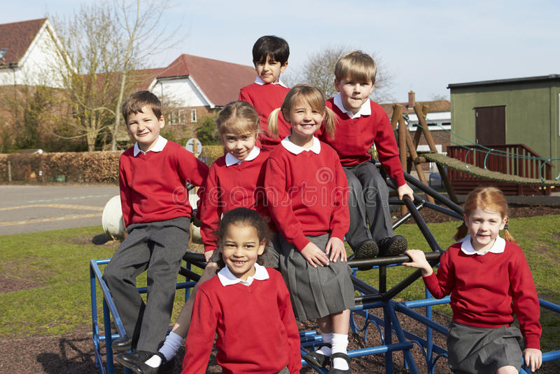 Porträt von Volksschule-Schülern auf kletternder Ausrüstung stockbild