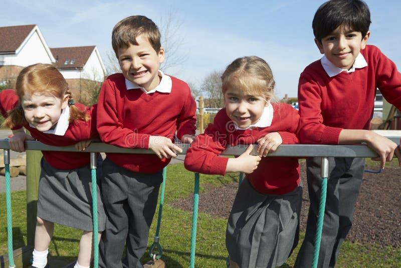Porträt von Volksschule-Schülern auf kletternder Ausrüstung stockfotos