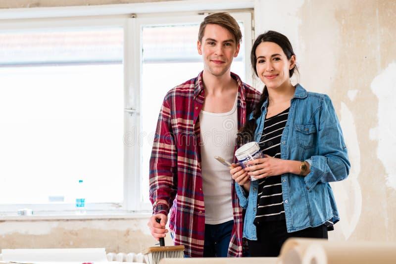 Porträt von Werkzeugen einer glücklichen jungen Paarholding für die Hauptumgestaltung lizenzfreie stockbilder