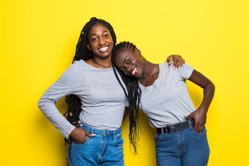 Porträt von zwei afrikanischen jungen Frauen, die über gelbem Hintergrund umarmen und lachen stockbilder