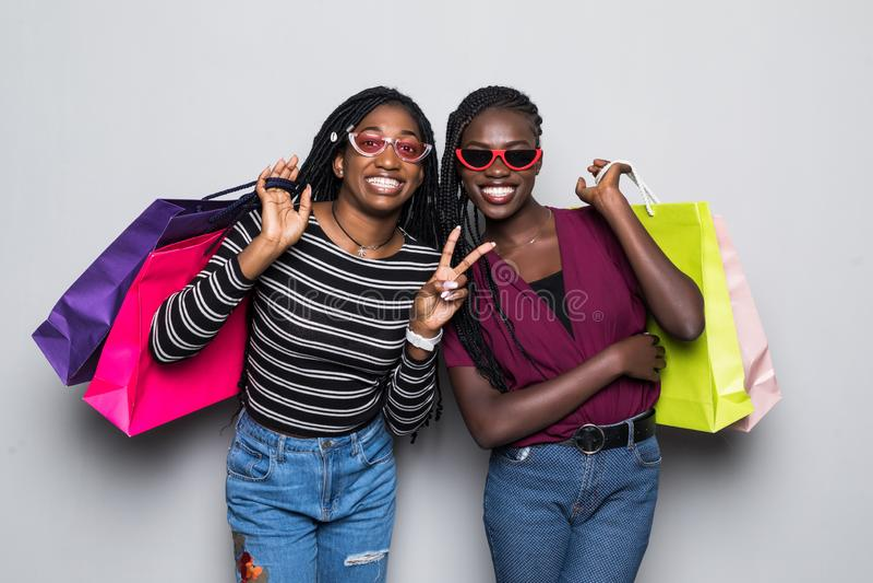 Porträt von zwei afrikanischen jungen Frauen, die Einkaufstaschen lokalisiert über grauem Hintergrund halten stockfotografie