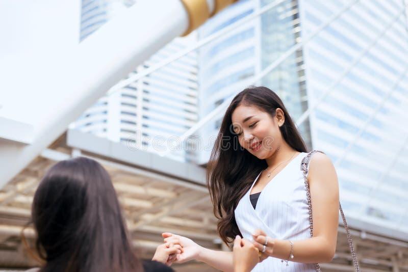 Porträt von zwei asiatischen besten Freunden, die zusammen glücklichem Händchenhalten in die Hauptstadt lächeln und glauben lizenzfreies stockfoto