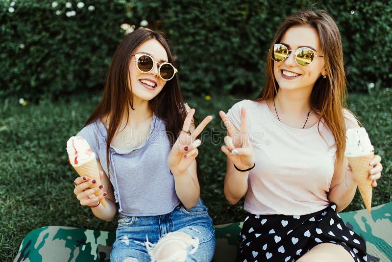 Porträt von zwei Frauen, die zusammen stehen, essend die Eiscreme, die auf dem Gras in der Stadtstraße sitzt stockfoto