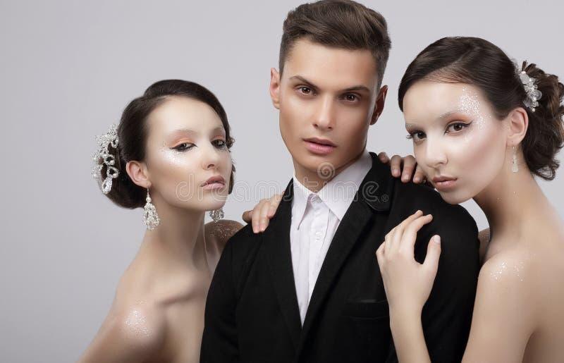 Porträt von zwei Frauen und von Männern einer, die elegante Kleidung auf Schwarzem tragen Zwei hübsche Frauen, die einen gutausse stockfotografie