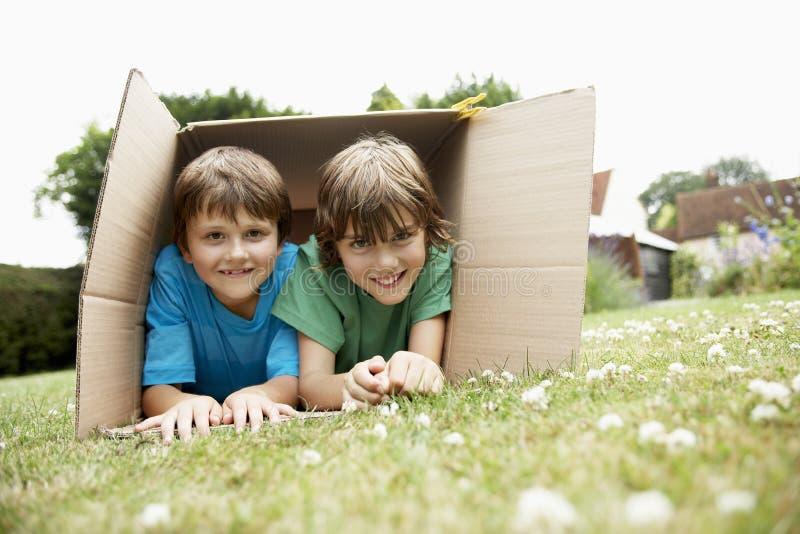 Porträt von zwei glücklichen Jungen, die in der Pappschachtel liegen lizenzfreies stockbild
