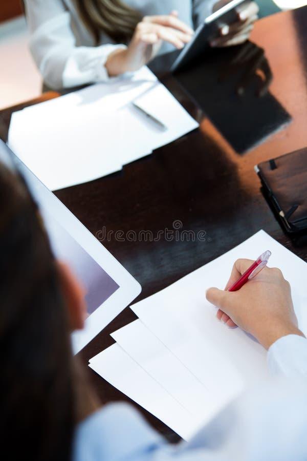 Porträt von zwei hübschen Geschäftsfrauen, die im Büro arbeiten lizenzfreies stockbild