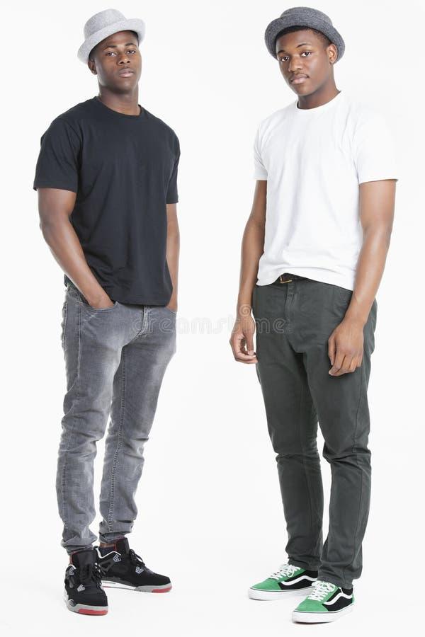 Porträt von zwei jungen Afroamerikanermännern in zufälligem über grauem Hintergrund lizenzfreie stockfotografie