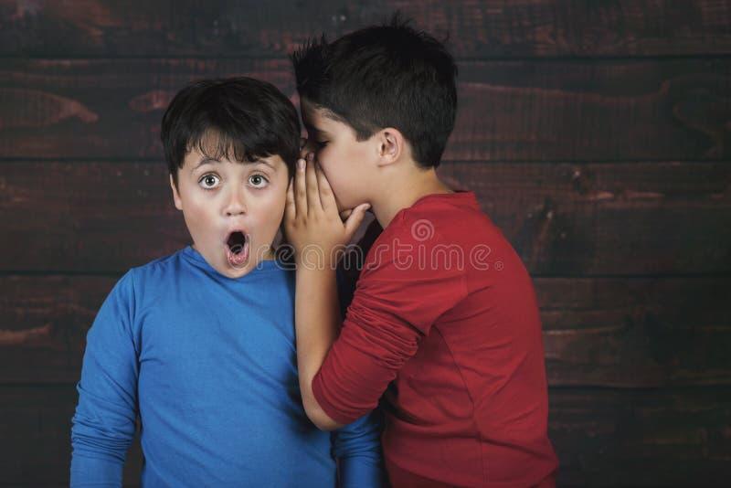 Porträt von zwei Jungen, die Geheimnis flüstern lizenzfreies stockfoto
