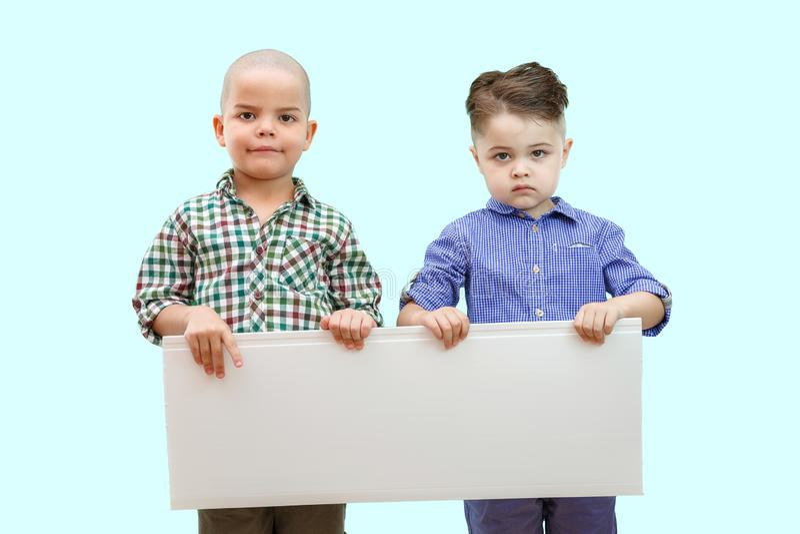 Porträt von zwei Jungen, die weißes Zeichen auf lokalisiertem Hintergrund halten stockbild