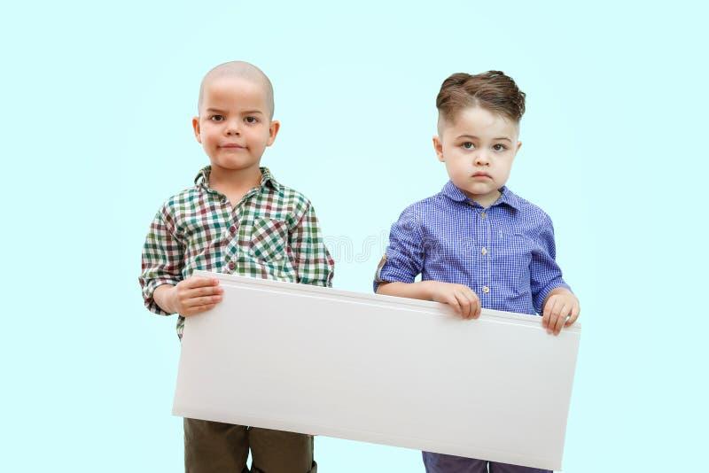 Porträt von zwei Jungen, die weißes Zeichen auf lokalisiertem Hintergrund halten lizenzfreie stockfotografie