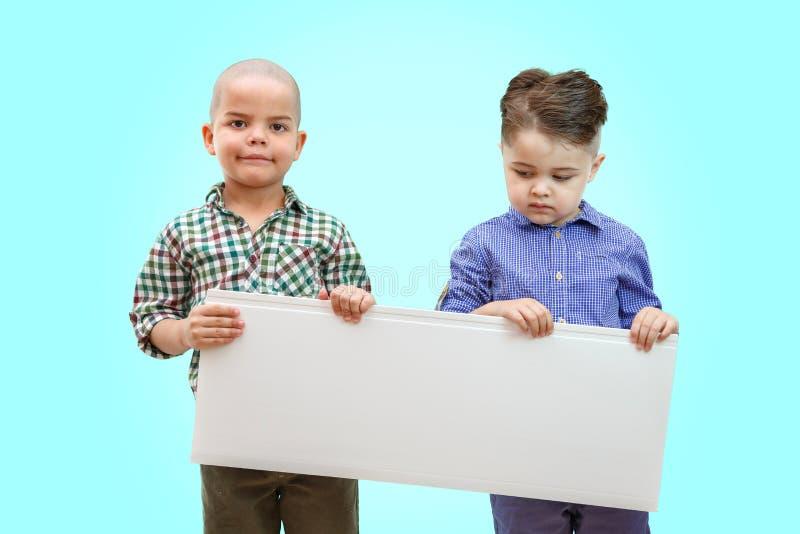Porträt von zwei Jungen, die weißes Zeichen auf lokalisiertem Hintergrund halten lizenzfreie stockbilder