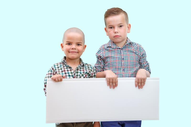 Porträt von zwei Jungen, die weißes Zeichen auf lokalisiertem Hintergrund halten lizenzfreie stockfotos