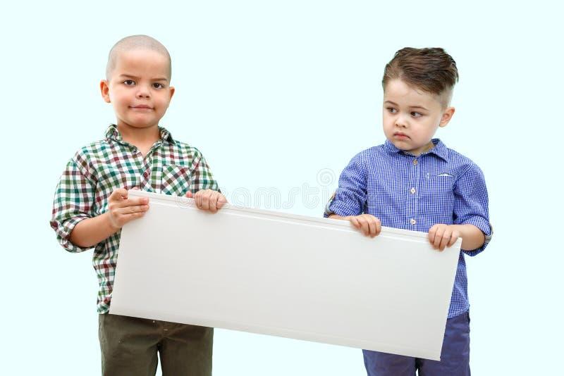 Porträt von zwei Jungen, die weißes Zeichen auf lokalisiertem Hintergrund halten lizenzfreies stockfoto