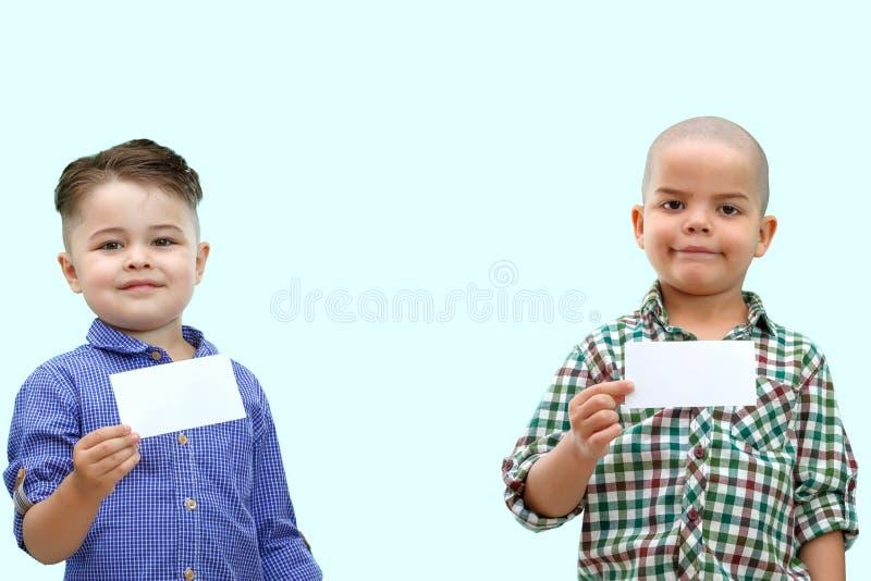 Porträt von zwei Jungen, die weißes Zeichen auf lokalisiertem Hintergrund halten stockfotos
