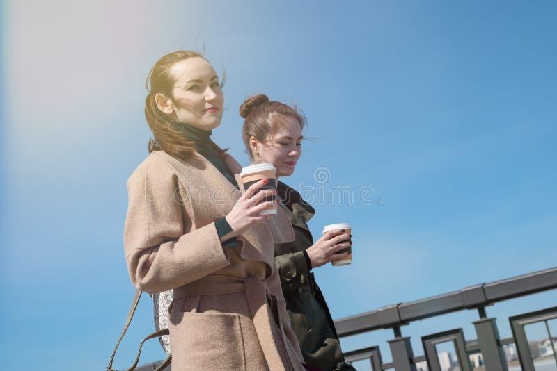 Porträt von zwei jungen Frauen in den modischen Mänteln und mit wegzunehmen den Tasse Kaffees, niedrigerer Winkel, Paparazzi stockbild