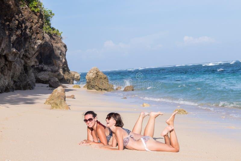 Porträt von zwei jungen Freundinnen liegen auf dem Seeufer, das Kamera und das Lachen betrachtet Kaukasische junge Frauen stockfoto