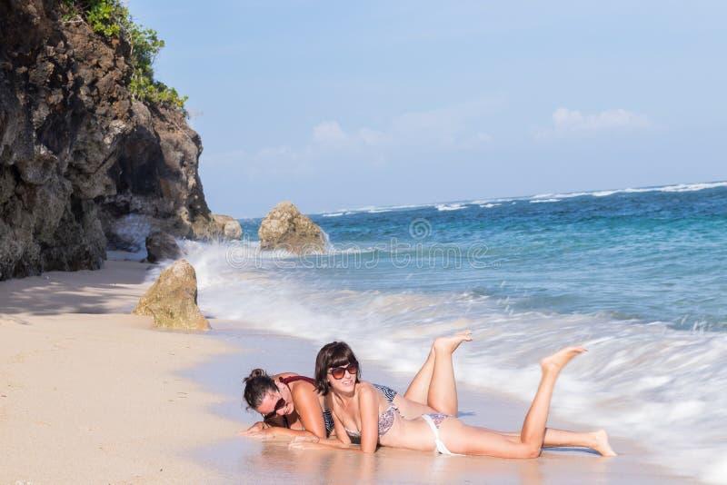 Porträt von zwei jungen Freundinnen liegen auf dem Seeufer, das Kamera und das Lachen betrachtet Kaukasische junge Frauen lizenzfreie stockfotografie