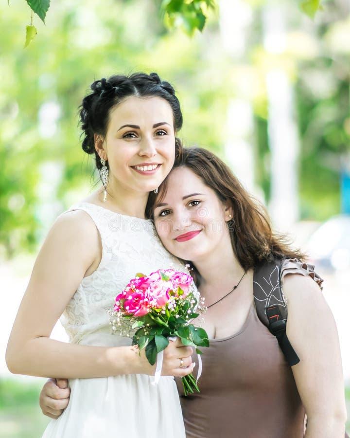 Porträt von zwei jungen hübschen Frauen, die im grünen Sommerpark sich umarmen Hübsche Fraubraut mit Blumenstrauß von Rosen und v lizenzfreies stockbild