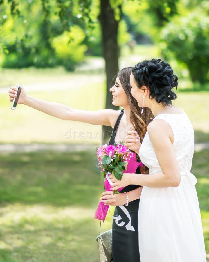 Porträt von zwei jungen hübschen Freundinnen, die selfie im grünen Sommerpark nehmen Hübsche Frauen Braut und Brautjungfer, die p lizenzfreies stockbild