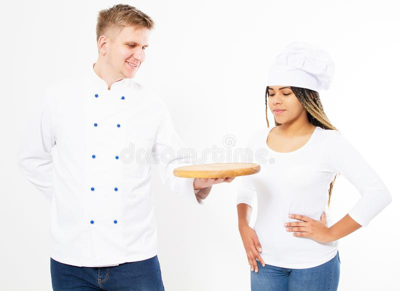 Porträt von zwei Köchen, sie das leere hölzerne Pizzabrett betrachtend lokalisiert über weißem Hintergrund stockbild
