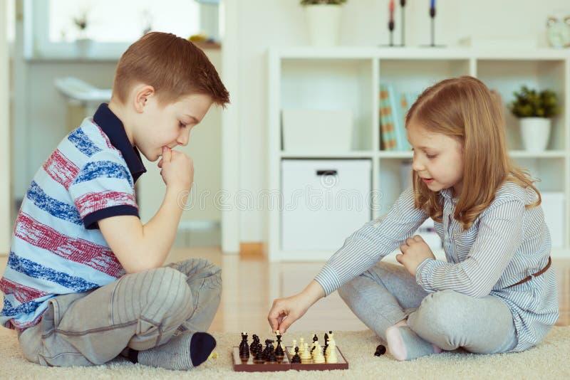 Porträt von zwei kleinen Kindern konzentrierte das Spielen des Schachs lizenzfreies stockfoto