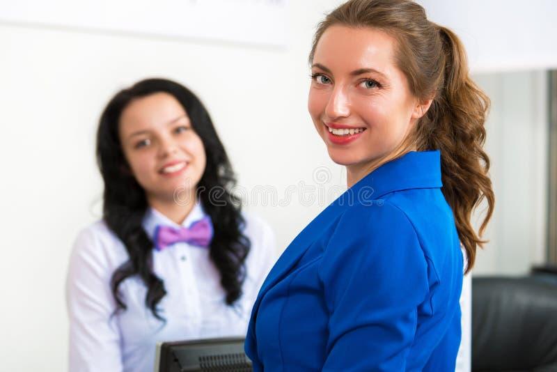 Porträt von zwei lächelnden Frauen im Büro lizenzfreie stockbilder