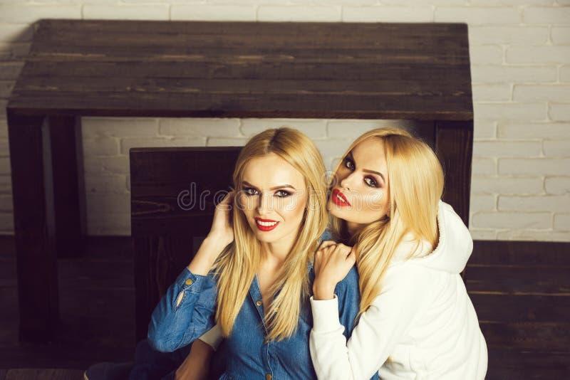 Porträt von zwei Mädchen der besten Freunde umfassen nahe Holztisch lizenzfreies stockbild