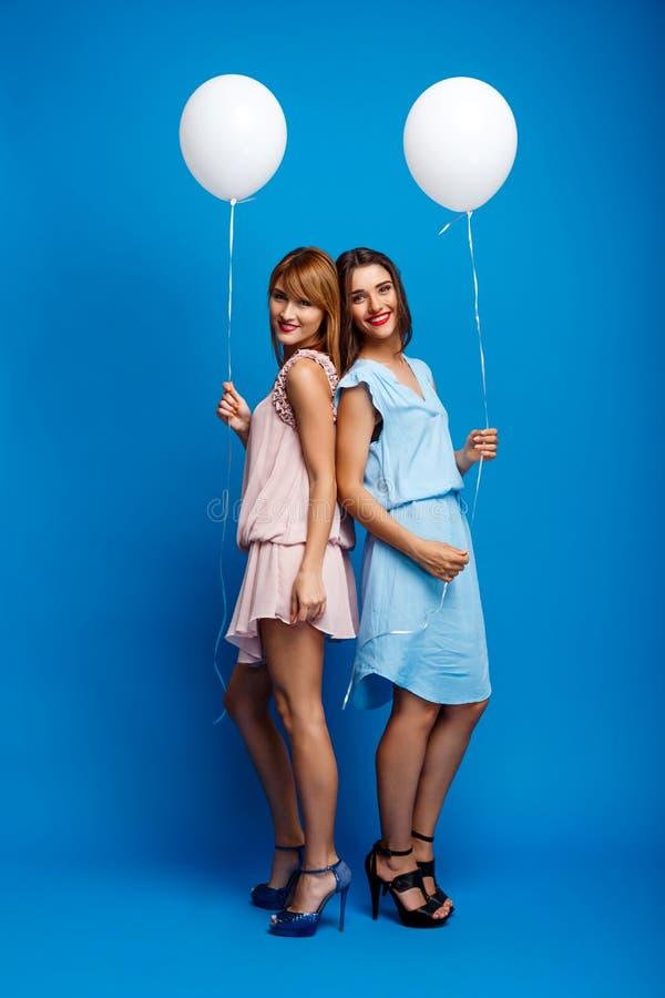 Porträt von zwei Mädchen, die an der Partei über blauem Hintergrund stillstehen lizenzfreies stockfoto