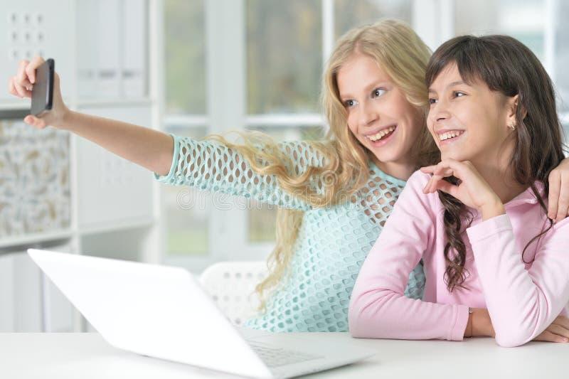 Porträt von zwei Mädchen mit Telefon und Laptop stockfotografie