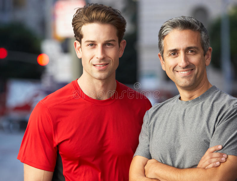 Porträt von zwei männlichen Läufern auf städtischer Straße stockbilder