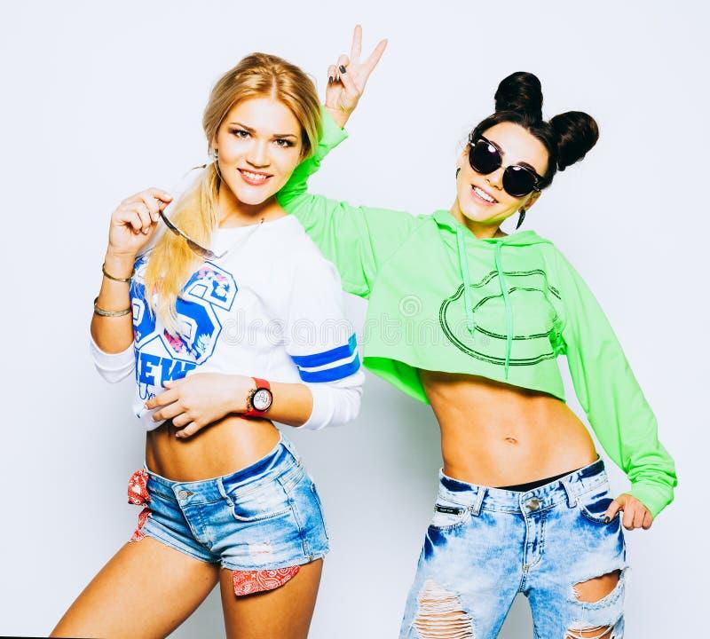 Porträt von zwei modischen kühlen Hippie-Mädchen im hellem Kalk und whigte Ausstattung, modische Frisuren und Make-up, Sonnenbril stockfotografie