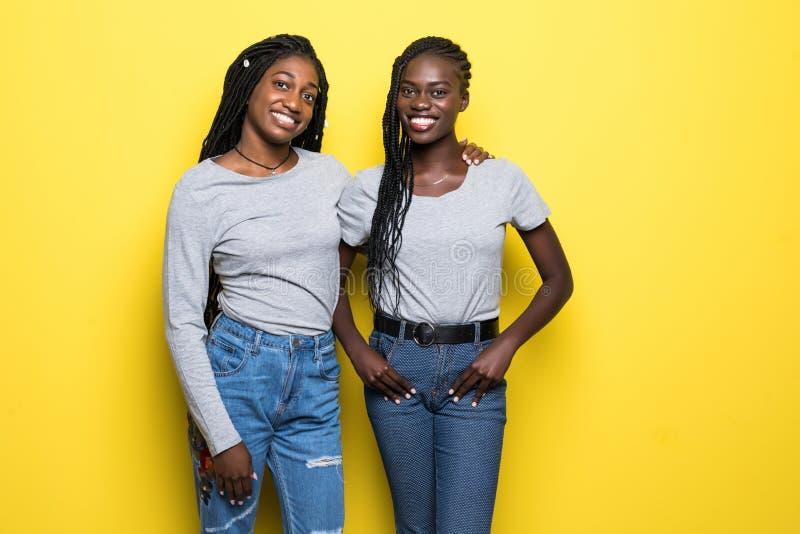 Porträt von zwei netten jungen afrikanischen Frauen, die zusammen stehen und die Kamera lokalisiert über gelbem Hintergrund betra lizenzfreies stockbild