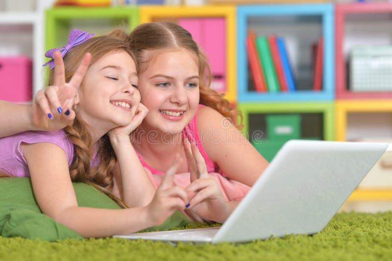 Porträt von zwei netten kleinen Mädchen, die Laptop verwenden lizenzfreie stockfotos