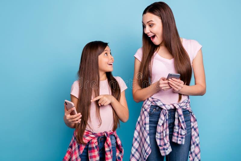Porträt von zwei netten netten reizend attraktiven reizenden netten heitren ekstatischen gerad-haarigen Mädchen, die neues Gerät  lizenzfreie stockfotografie
