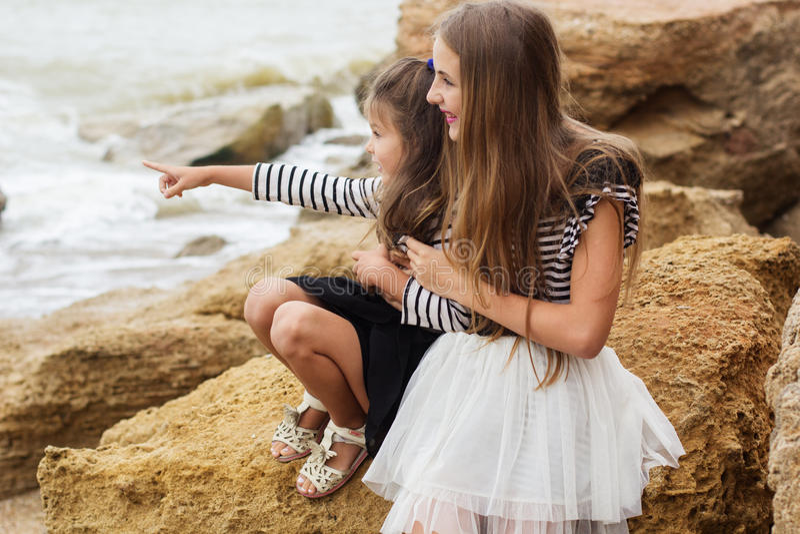 Porträt von zwei netten Schwestern, die auf dem Strand sitzen lizenzfreie stockbilder