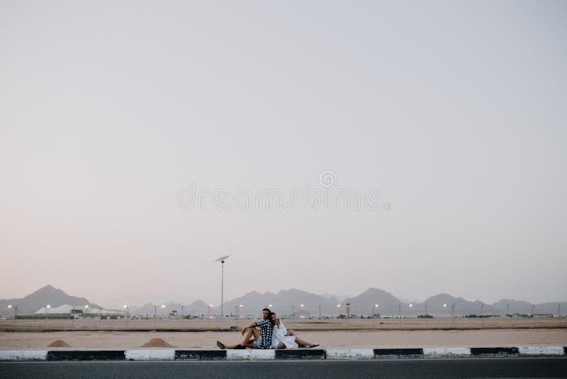 Portr?t von zwei Reisenden, die auf der Stra?e, auf eine Fahrt wartend stillstehen und genie?t sch?ne Landschaft Junges attraktiv lizenzfreie stockbilder