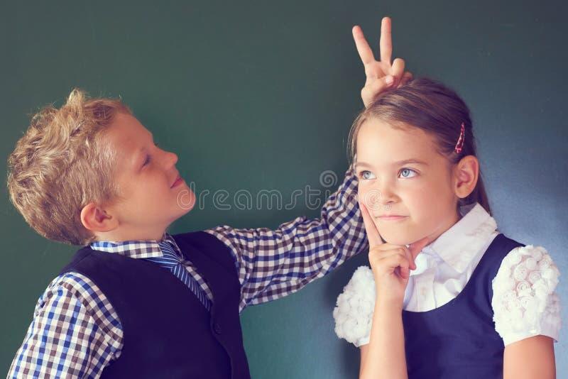 Porträt von zwei schönen Europäerkindern Junge und Mädchen in der Schuluniform, die nahe bei der Tafel steht Junge zeigt Hörner lizenzfreies stockfoto