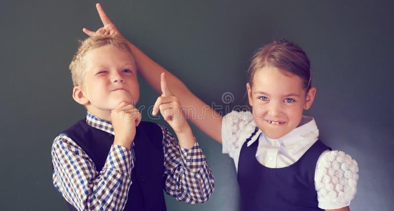 Porträt von zwei schönen Europäerkindern Junge und Mädchen in der Schuluniform, die nahe bei der Tafel steht Mädchen zeigt Hörner lizenzfreie stockfotografie