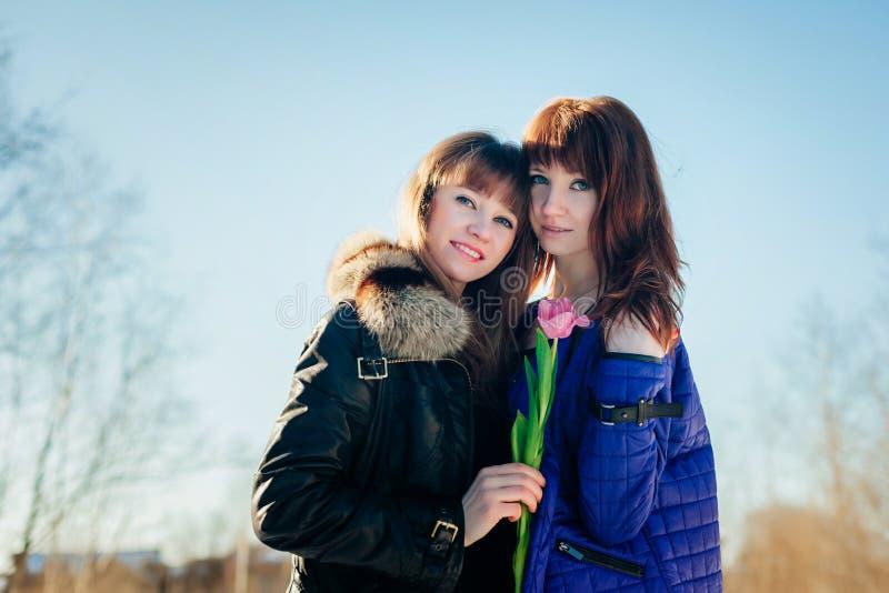 Porträt von zwei schönen Mädchen gegen einen klaren Frühlingshimmel stockbilder